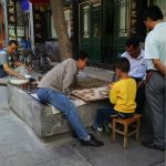 Chinese chess is played on the side of a tree on LiuLiChang East Road, the main pedestrian road at LiuLiChang.